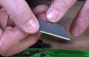 Checking for any design in the blade of a box cutter to ensure it is seated properly.